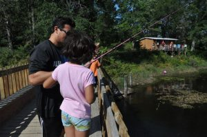 Family Fishing with cabin in background